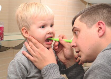 a young boy brushing his teeth with a toothbrush in his mouth