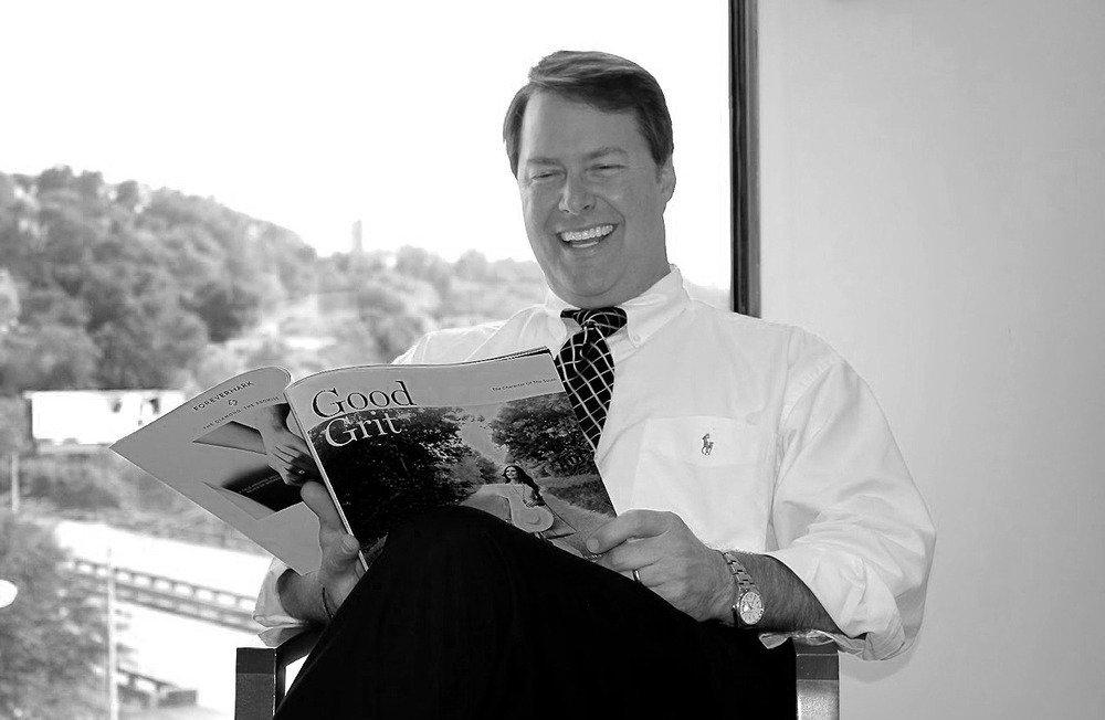 a man in a suit and tie reading a magazine
