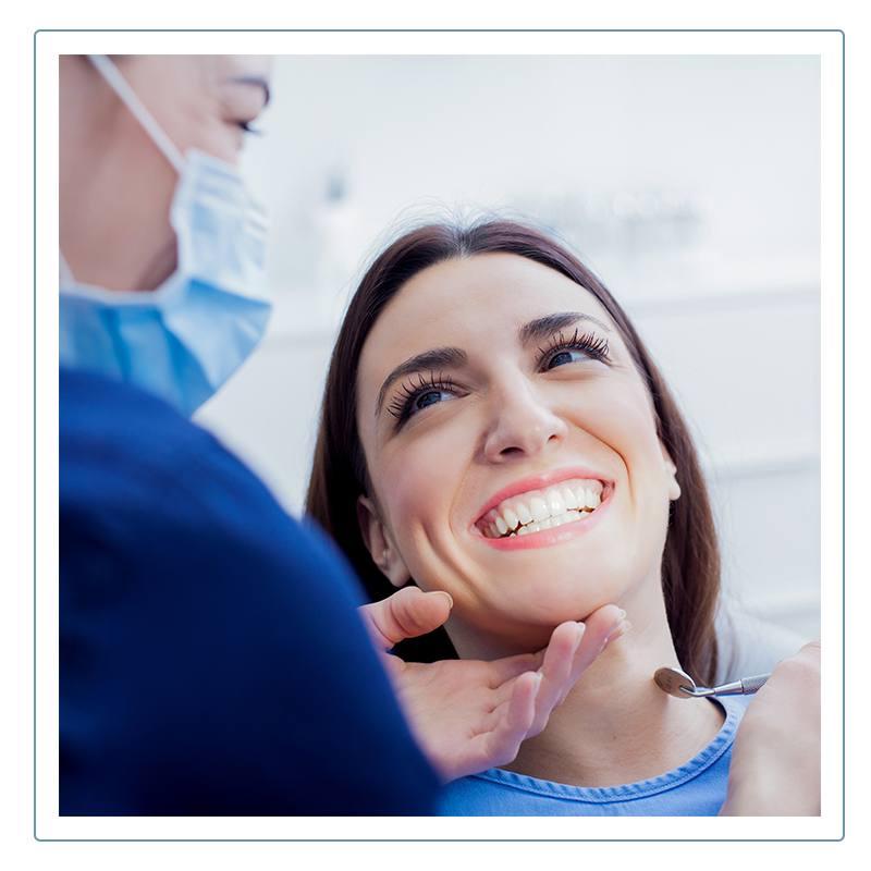 dentist examines woman's teeth