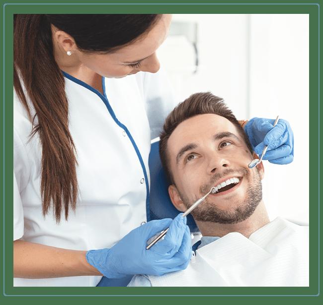 female dentist works on a man's teeth