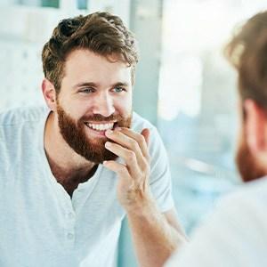 a man in a white shirt inspects his teeth